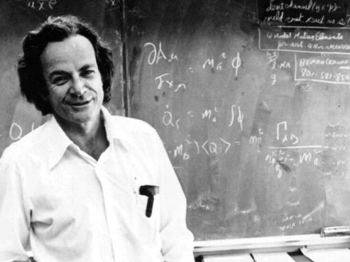 richard feynman standing in front of a blackboard