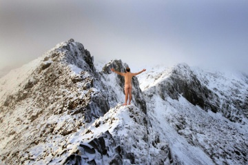 naked man standing on snow-covered mountain