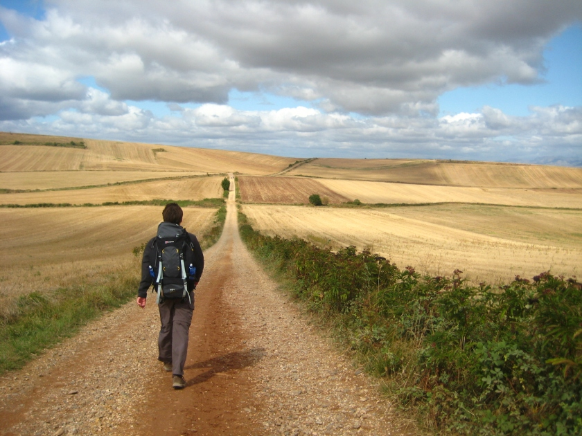 Man walking along lonely trail stretchin into the distance